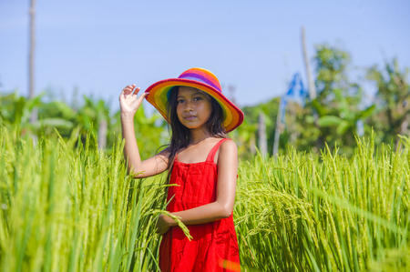 sweet happy and beautiful 7 or 8 years old child in Summer hat and cute red dress having fun outdoors smiling cheerful at rice field in young girl enjoying holidays concept 版權商用圖片