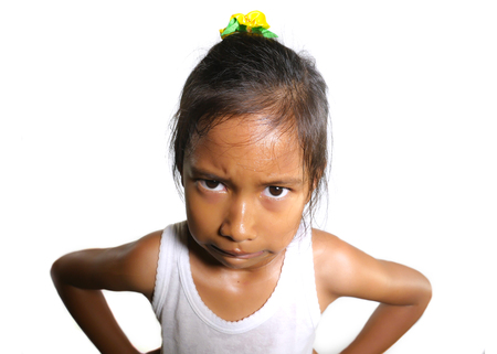 head and shoulders portrait of sweet upset and disappointed 7 years old Asian girl looking intense to the camera feeling angry and unhappy in moody pose isolated on white background