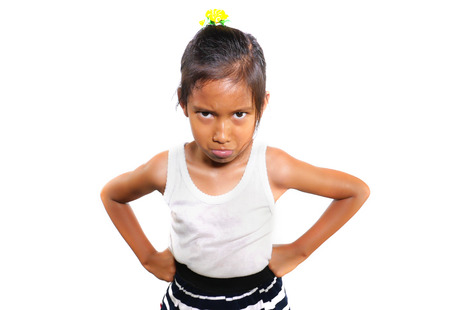 funny portrait of sweet upset and disappointed 7 years old Asian girl looking intense to the camera feeling angry and unhappy in moody pose isolated on white background