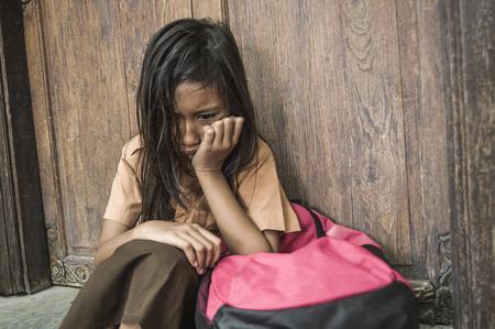 7 oder 8 Jahre Kind in Schuluniform, das draußen auf dem Boden sitzt und traurig und deprimiert weint, ihren Rucksack hält und unter Mobbing und Missbrauch leidet, sich allein und hilflos als verängstigtes Schulmädchen fühlen Standard-Bild