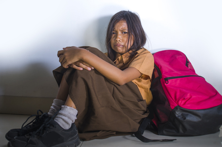 dramatic portrait of sad and depressed 8 or 9 years old child in school uniform sitting on the floor with her bad crying helpless feeling scared and desperate suffering bullying and abuse