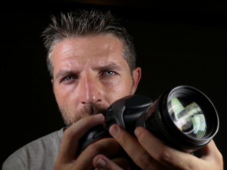close up portrait of attractive and handsome man on his 30d holding professional reflex photo camera next to his face isolated on black background in photography hobby and job