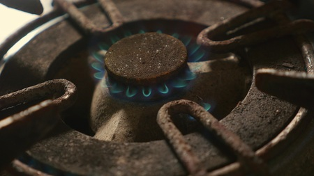 close up detail shot of old rusty kitchen stove ring burning after switched on fire with lighter flame in dangerous gas energy and domestic cooking concept