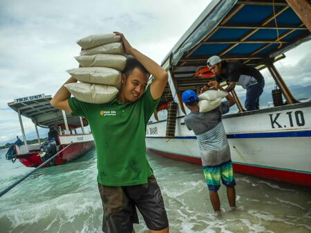 Gili Trawangan island  INDONESIA - March 8th 2019. Boats supply 247 all kind of stuff to compensate the lack of resources of the island. Here the crew unloading rice