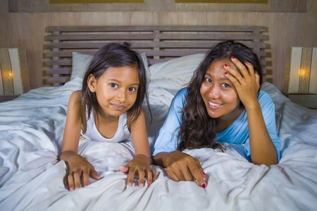 lifestyle bedroom portrait of happy Asian woman at home posing with her beautiful 8 years old  daughter in bed smiling playful cheerful in mother and child love and parenting concept