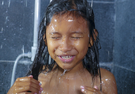 lifestyle home portrait of sweet and happy female child having shower in the bathroom washing her hair in hygiene education concept