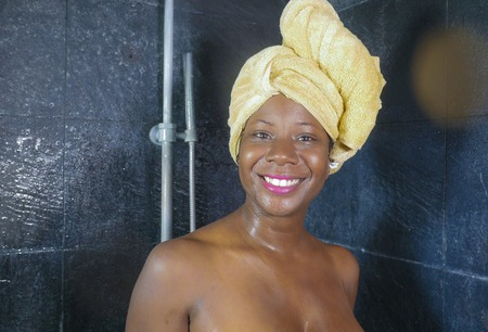domestic lifestyle portrait of young beautiful black afro American woman having a shower with her head wrapped in a towel smiling cheerful in hygiene and beauty concept