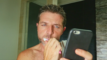 lifestyle portrait of young handsome and attractive internet addict man at home bathroom with towel on shoulder washing teeth with toothbrush using online mobile phone in social media addiction 写真素材 - 118641926