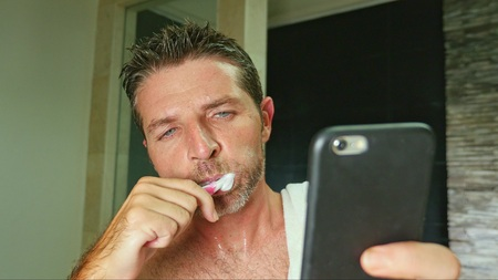 lifestyle portrait of young handsome and attractive internet addict man at home bathroom with towel on shoulder washing teeth with toothbrush using online mobile phone in social media addiction 写真素材 - 118641934