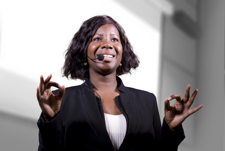 young attractive and confident black African American business woman with headset speaking in auditorium at corporate training event or seminar giving motivation and success coaching conference 免版税图像 - 118924528