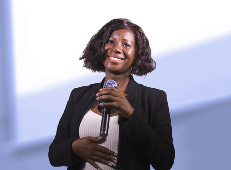 young attractive and confident black afro American business woman with microphone speaking in auditorium at corporate event or seminar giving motivation and success coaching conference