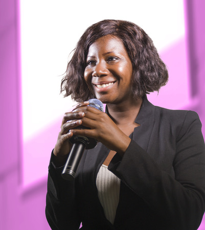young attractive and confident black African American business woman with microphone speaking in auditorium at corporate event or seminar giving motivation and success coaching conference Foto de archivo