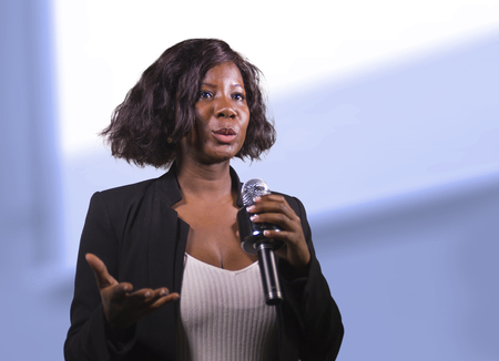 Joven mujer de negocios afroamericana negra atractiva y segura con micrófono hablando en auditorio en evento corporativo o seminario dando motivación y conferencia de coaching de éxito Foto de archivo