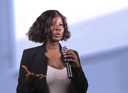 junge attraktive und selbstbewusste schwarze afroamerikanische Geschäftsfrau mit Mikrofon, die im Auditorium bei Firmenveranstaltungen oder Seminaren spricht, die Motivation und Erfolgscoaching-Konferenz geben Standard-Bild