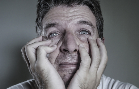 head and shoulders dramatic portrait of young man crying in pain suffering depression and anxiety problem feeling stressed and desperate in looking devastated in despair emotion concept Stock Photo