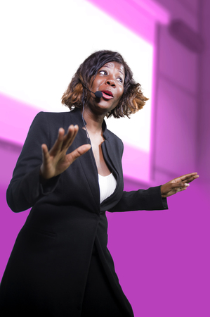 young attractive and confident black afro American business woman with microphone speaking in auditorium at corporate seminar event giving success coaching conference or political rally