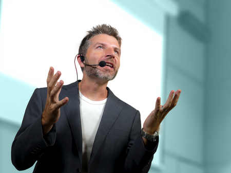 young attractive and confident successful man with headset speaking at corporate business coaching and training auditorium conference room talking giving motivation training from speaker stage Standard-Bild