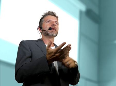 young attractive and confident successful man with headset speaking at corporate business coaching and training auditorium conference room talking giving motivation training from speaker stage Imagens