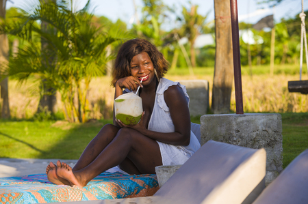 young happy and attractive black afro American woman lying on pool hammock at tropical beach resort chilling relaxed drinking coconut water in Summer holidays travel and tourism concept