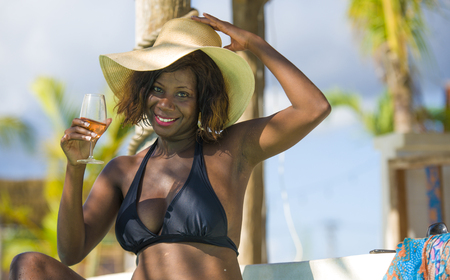 lifestyle fresh portrait of young happy and attractive black afro American woman in bikini and Summer hat drinking glass of wine at luxury tropical beach resort enjoying holidays trip Stock Photo