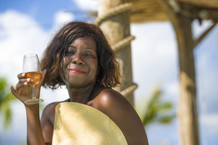 lifestyle fresh portrait of young happy and attractive black African American woman in bikini and Summer hat drinking glass of wine at luxury tropical beach resort enjoying holidays trip