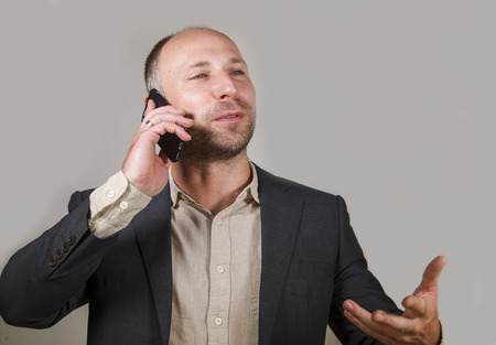 young happy and confident successful businessman talking on mobile phone having business conversation with cellphone smiling cheerful in corporate job and entrepreneur success concept