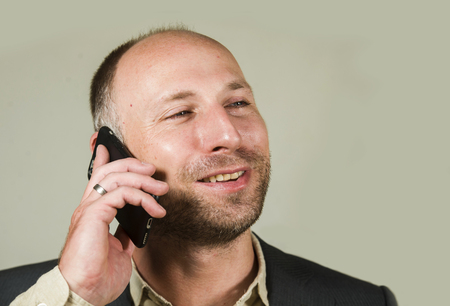 young happy and confident successful businessman talking on mobile phone having business conversation with cellphone smiling cheerful in corporate job and entrepreneur success concept Stockfoto