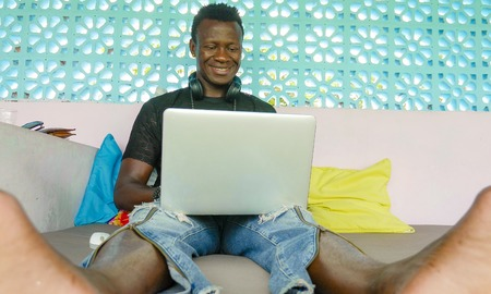 young handsome and happy hipster black African American business man working with laptop computer and headphones smiling satisfied and cool in digital nomad entrepreneur internet job Imagens