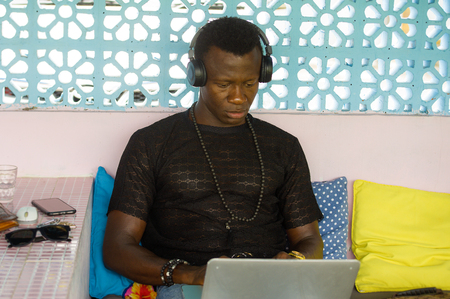 young attractive and hipster black African American business man networking with laptop computer and headphones concentrated and thoughtful in digital nomad internet job and online success