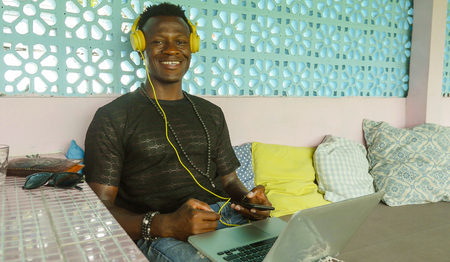 young happy and attractive black afro American hipster man networking relaxed with mobile phone and laptop computer smiling in digital nomad job success and internet work lifestyle Foto de archivo