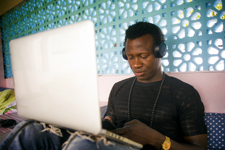 young cool and attractive black African American hipster man with headphones networking relaxed with mobile phone and laptop computer in digital nomad job and internet work lifestyle