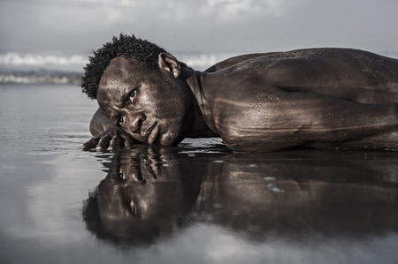 artistic expressive portrait of young attractive and sexy black African American man with athletic muscular body posing cool in sea water on desert beach in male beauty and holidays concept Stok Fotoğraf