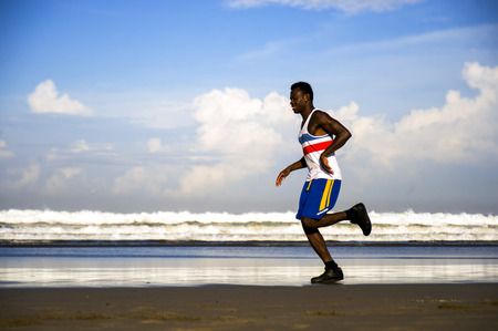 healthy lifestyle portrait of young athletic and attractive black African American runner man doing running workout training on desert beach in fitness and wellness isolated on blue sky Stockfoto