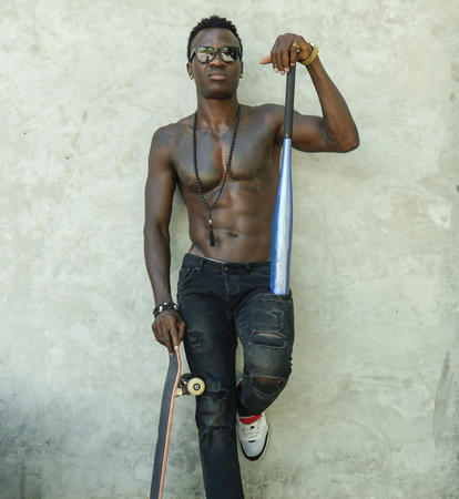 young attractive and handsome black afro American man with fit muscular body and six pack holding baseball bat and skate board posing cool urban badass and bad boy attitude on street Stock Photo