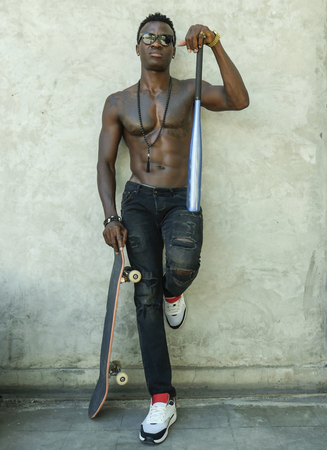 young attractive and handsome black African American man with fit muscular body and six pack holding baseball bat and skate board posing cool urban badass and bad boy attitude on street