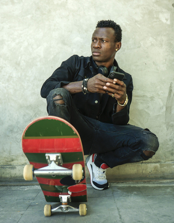 urban lifestyle portrait of young attractive and serious black afro American man squatting on skate board at grunge street corner posing in badass bad boy attitude using mobile phone 版權商用圖片