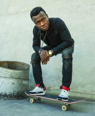 urban lifestyle portrait of young attractive and serious black afro American man squatting on skate board at grunge street corner looking cool posing in badass bad boy attitude in city life