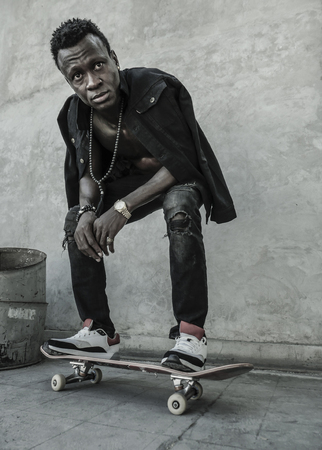 urban lifestyle portrait of young attractive and serious black afro American man squatting on skate board at grunge street corner looking cool posing in badass bad boy attitude in city life  Archivio Fotografico