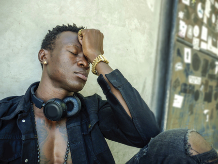 urban lifestyle portrait of young sad and depressed black afro American man sitting outdoors on street corner feeling upset and frustrated suffering depression problem