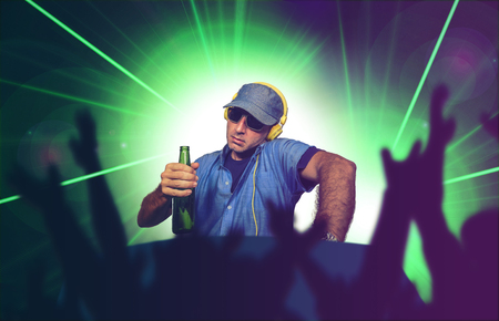 young happy and cool DJ playing music at party event in night club mixing techno songs on laser and flash lights background cheered with hands by clubbing and dancing crowd