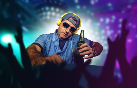 young happy and cool deejay  playing music at party event in night club mixing techno songs on laser and flash lights background cheered with hands by clubbing and dancing crowd