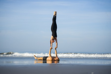 young attractive and beautiful acrobat couple practicing acroyoga exercise concentrated keeping balance practicing yoga on the beach in relaxation and meditation concept and healthy lifestyle