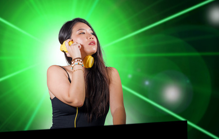 young beautiful and attractive Asian Korean DJ woman remixing music at night club wearing headphones isolated on flashes and laser lights background in clubbing party and DJ lifestyle concept