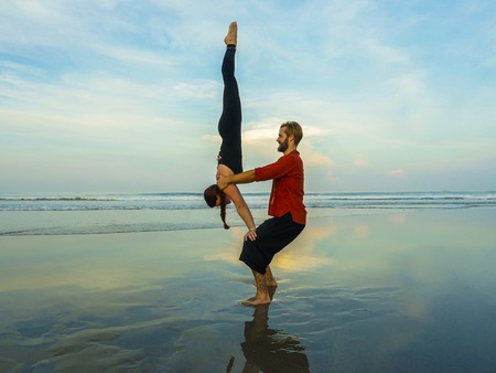 healthy and attractive fit couple of acrobats doing acroyoga balance and meditation exercise on beautiful desert beach practicing balance and harmony posing in healthy lifestyle and yoga concept
