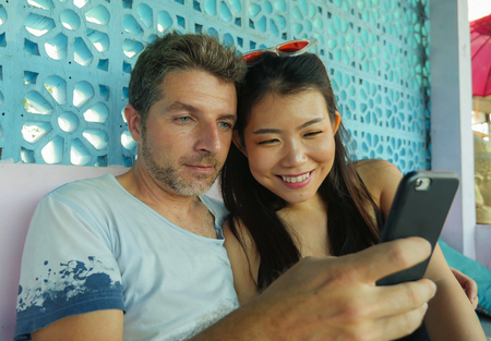 young beautiful and happy mixed ethnicity couple in love smiling cheerful with handsome Caucasian man and beautiful Asian Korean woman using mobile phone together at coffee shop