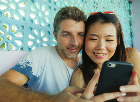 young beautiful and happy mixed ethnicity couple in love smiling cheerful with handsome Caucasian man and beautiful Asian Chinese woman using mobile phone together at coffee shop