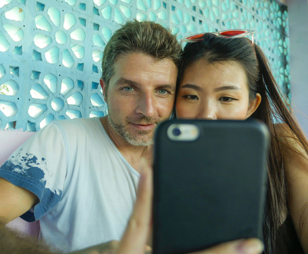 young beautiful and happy mixed ethnicity couple in love smiling cheerful with handsome Caucasian man and beautiful Asian Japanese woman using mobile phone together at coffee shop