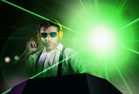 young attractive and cool DJ in shirt and suspenders remixing music at night club using headphones in party strobo and laser lights background in clubbing and nightlife concept Standard-Bild