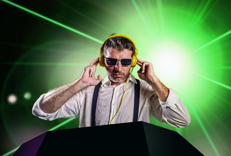 young attractive and cool DJ in shirt and suspenders remixing music at night club using headphones in party strobo and laser lights background in clubbing and nightlife concept Stock Photo