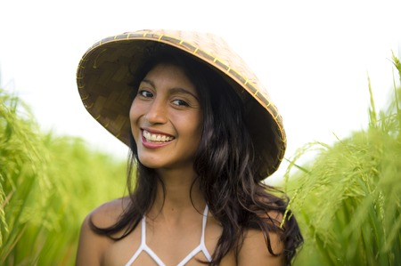 young happy and beautiful latin woman playing with traditional Asian farmer hat smiling having fun posing isolated on green rice field in Asia tourist trip and Summer holidays travel Stock Photo